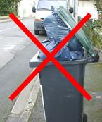 Une poubelle couvercle ouvert avec des sacs d'ordures dépassant