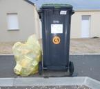 Une poubelle couvercle fermé présentée poignée face à la route