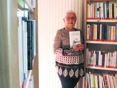 Martine de la Bibliothèque Les mille et une pages tenant un livre devant un rayonnage